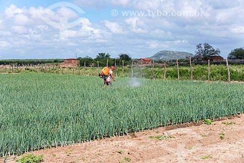 Trabalhador rural sem equipamento de proteção individual aplicando defensivos em plantação de cebola irrigada com água captada do Rio São Francisco  - Cabrobó - Pernambuco (PE) - Brasil