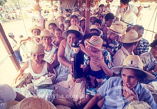 Detalhe de romeiros com a imagem de Padre Cícero em transporte irregular de passageiros em caminhão - também chamado de Pau de arara  - Juazeiro do Norte - Ceará (CE) - Brasil