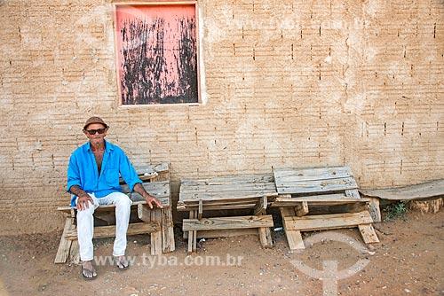 Homem sentado em móveis feitos de restos de madeira em frente à sua casa próximo ao Reservatório Cacimba Nova  - Custódia - Pernambuco (PE) - Brasil