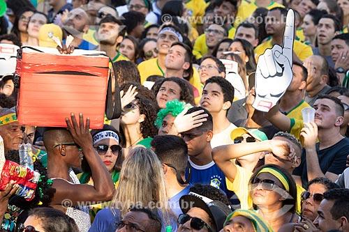 Detalhe de vendedor ambulante em meio à torcida pela Seleção Brasileira no Boulevard Olímpico durante o jogo entre Brasil x Bélgica pela Copa do Mundo 2018 - jogo em que o Brasil foi eliminado  - Rio de Janeiro - Rio de Janeiro (RJ) - Brasil