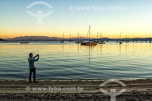 Homem fotografando a orla da Praia de Santo Antônio de Lisboa durante o pôr do sol  - Florianópolis - Santa Catarina (SC) - Brasil