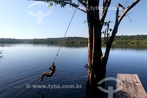 Menino ribeirinho da comunidade ribeirinha tumbira brincando no Rio Negro - Parque Nacional de Anavilhanas  - Novo Airão - Amazonas (AM) - Brasil