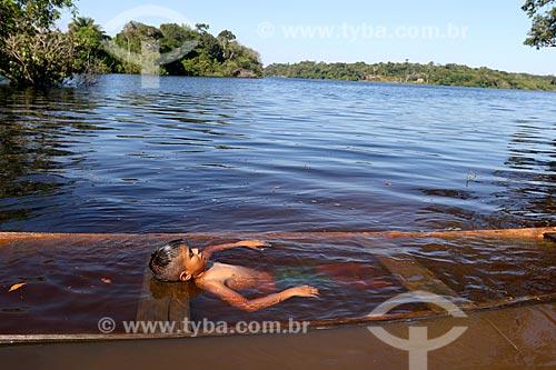 Menino ribeirinho da comunidade ribeirinha tumbira brincando em canoa quase encoberta no Rio Negro - Parque Nacional de Anavilhanas  - Novo Airão - Amazonas (AM) - Brasil