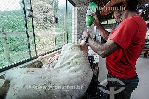 Homem temperando porco para assar no Sítio Triunfo  - Maricá - Rio de Janeiro (RJ) - Brasil