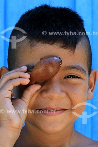 Menino da tribo Baré - Estevão Melo Amazonas - segurando artesanato indígena na Comunidade Boa Esperança - Reserva de Desenvolvimento Sustentável Puranga Conquista  - Manaus - Amazonas (AM) - Brasil