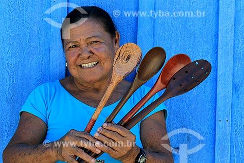 Detalhe de artesã Uaulina Garrido segurando colheres de pau - artesanato indígena da tribo Baré da Comunidade Boa Esperança na Reserva de Desenvolvimento Sustentável Puranga Conquista  - Manaus - Amazonas (AM) - Brasil