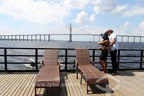 Casal observando o Rio Negro a partir de barco com a Ponte Rio Negro ao fundo  - Manaus - Amazonas (AM) - Brasil