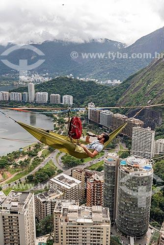 Homem deitado na rede em fita de slackline com uma garrafa de vinho no Morro do Cantagalo  - Rio de Janeiro - Rio de Janeiro (RJ) - Brasil