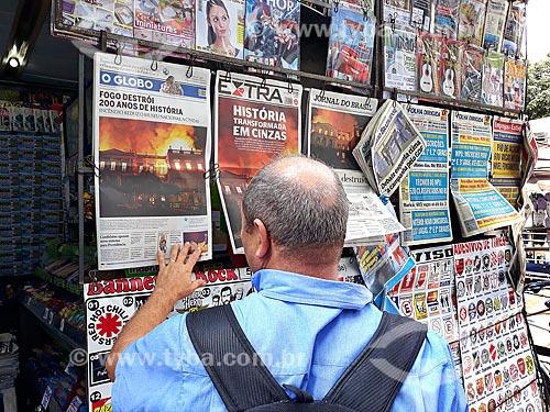 Homem lendo jornais expostos na banca de jornal após o incêndio de grandes proporções que destruiu quase a totalidade do acervo histórico  - Rio de Janeiro - Rio de Janeiro (RJ) - Brasil