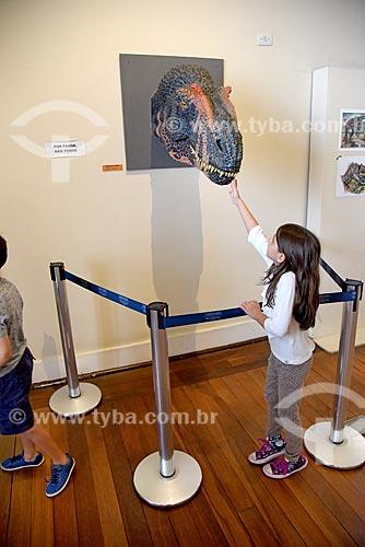 Menina interagindo com réplica de dinossauro em exibição no Museu Nacional - antigo Paço de São Cristóvão  - Rio de Janeiro - Rio de Janeiro (RJ) - Brasil