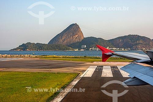 Detalhe de asa de avião na pista do Aeroporto Santos Dumont com o Pão de Açúcar ao fundo  - Rio de Janeiro - Rio de Janeiro (RJ) - Brasil