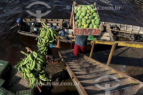 Homem carregando cachos de banana e mamão na cabeça no Porto de Manaus Moderna  - Manaus - Amazonas (AM) - Brasil