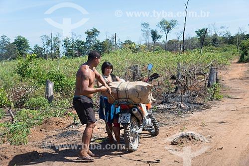 Casal indígena da aldeia Aiha da tribo Kalapalo carregando mandioca em motocicleta para transportar para a aldeia - ACRÉSCIMO DE 100% SOBRE O VALOR DE TABELA  - Querência - Mato Grosso (MT) - Brasil