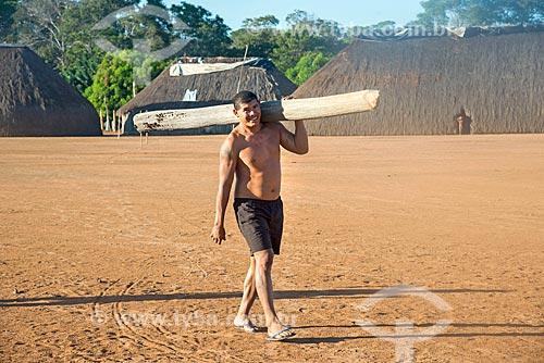 Índio na aldeia Aiha da tribo Kalapalo carregando tronco - ACRÉSCIMO DE 100% SOBRE O VALOR DE TABELA  - Querência - Mato Grosso (MT) - Brasil