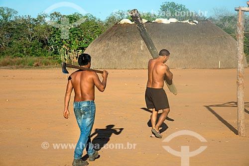 Índio na aldeia Aiha da tribo Kalapalo carregando um machado e outro um tronco - ACRÉSCIMO DE 100% SOBRE O VALOR DE TABELA  - Querência - Mato Grosso (MT) - Brasil
