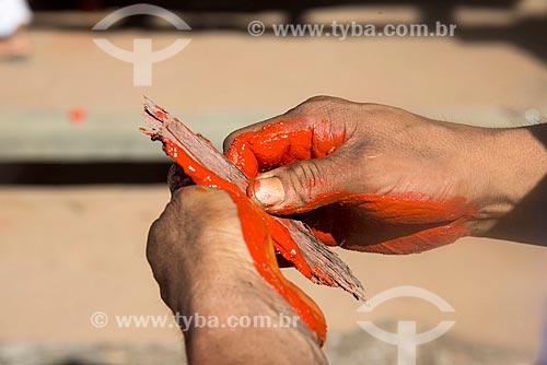 Detalhe de índio na aldeia Aiha da tribo Kalapalo produzindo tinta para pintura corporal com urucum - ACRÉSCIMO DE 100% SOBRE O VALOR DE TABELA  - Querência - Mato Grosso (MT) - Brasil