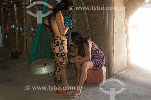 Detalhe de jovem mulher indígena na aldeia Aiha da tribo Kalapalo fazendo pintura corporal para a Dança Yamaricumã - ACRÉSCIMO DE 100% SOBRE O VALOR DE TABELA  - Querência - Mato Grosso (MT) - Brasil