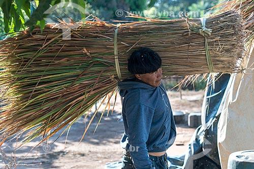 Índio carregando sapé  para a cobertura de oca na aldeia Aiha da tribo Kalapalo - ACRÉSCIMO DE 100% SOBRE O VALOR DE TABELA  - Querência - Mato Grosso (MT) - Brasil