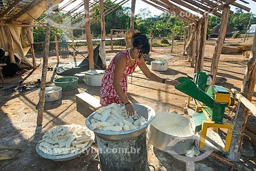 Mulher indígena na aldeia Aiha da tribo Kalapalo usando máquina para ralando mandioca - ACRÉSCIMO DE 100% SOBRE O VALOR DE TABELA  - Querência - Mato Grosso (MT) - Brasil