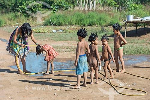 Antropóloga lavando os cabelos de crianças com shampoo anti piolho na aldeia Aiha da tribo Kalapalo - ACRÉSCIMO DE 100% SOBRE O VALOR DE TABELA  - Querência - Mato Grosso (MT) - Brasil