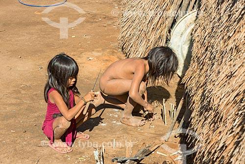 Meninas indígenas brincando com facão e gravetos na aldeia Aiha da tribo Kalapalo - ACRÉSCIMO DE 100% SOBRE O VALOR DE TABELA  - Querência - Mato Grosso (MT) - Brasil