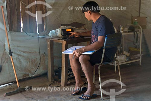 Índio com rádio de comunicação no posto de saúde na aldeia Aiha da tribo Kalapalo - ACRÉSCIMO DE 100% SOBRE O VALOR DE TABELA  - Querência - Mato Grosso (MT) - Brasil