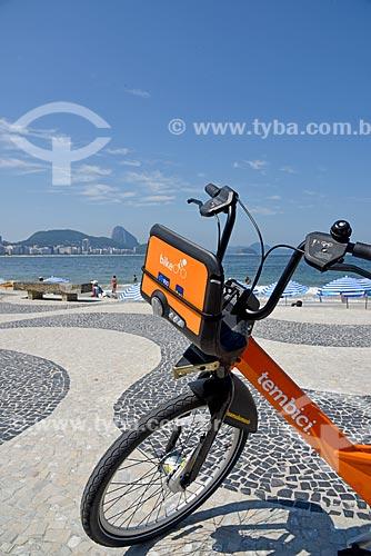 Detalhe de bicicleta pública - para aluguel - no calçadão da Praia de Copacabana - Posto 6 - com o Pão de Açúcar ao fundo  - Rio de Janeiro - Rio de Janeiro (RJ) - Brasil