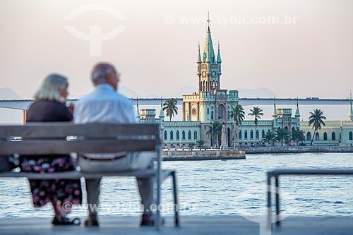 Casal de idosos observando a vista da Baía de Guanabara a partir da Praça XV de Novembro no local conhecido no século XIX como Cais Pharoux com o Castelo da Ilha Fiscal ao fundo  - Rio de Janeiro - Rio de Janeiro (RJ) - Brasil