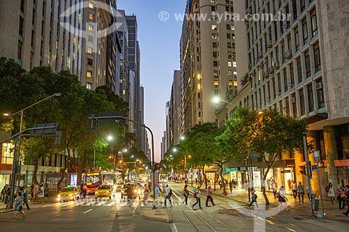 Pedestres atravessando na esquina da Avenida Rio Branco com a Avenida Nilo Peçanha durante o anoitecer  - Rio de Janeiro - Rio de Janeiro (RJ) - Brasil