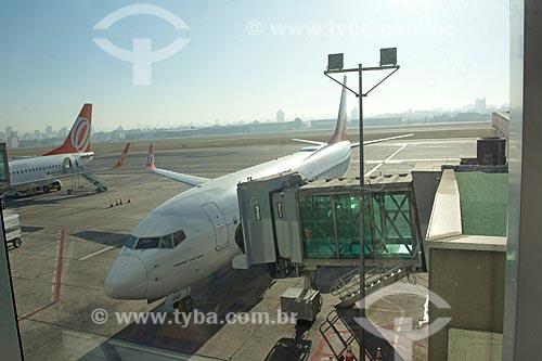 Avião da GOL - Linhas Aéreas Inteligentes - na pista do Aeroporto Internacional de São Paulo-Guarulhos Governador André Franco Montoro (1985) com passarela de acesso a aeronaves  - Guarulhos - São Paulo (SP) - Brasil