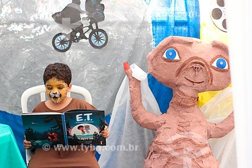 Menino lendo durante a feira cultural do Colégio Nossa Senhora da Ressurreição  - Rio de Janeiro - Rio de Janeiro (RJ) - Brasil