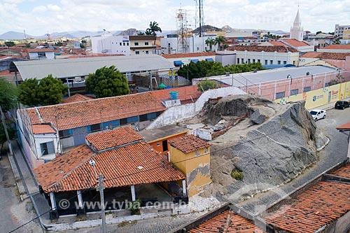 Foto feita com drone de construção ao redor de inselberg do Monumento Natural dos Monólitos de Quixadá ao fundo  - Quixadá - Ceará (CE) - Brasil