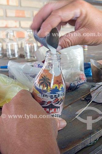 Detalhe de artesão fazendo garrafas de areia colorida  - Beberibe - Ceará (CE) - Brasil