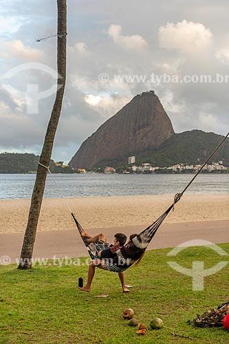 Casal deitado em uma rede na orla da Praia do Flamengo com o Pão de Açúcar ao fundo  - Rio de Janeiro - Rio de Janeiro (RJ) - Brasil