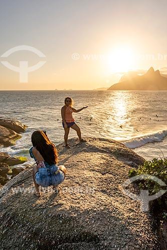 Mulher fazendo uma fotografia em perspectiva forçada durante o pôr do sol na Pedra do Arpoador  - Rio de Janeiro - Rio de Janeiro (RJ) - Brasil