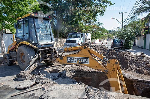 Escavadeira da Companhia Estadual de Águas e Esgotos (CEDAE) fazendo o reparo na tubulação de esgoto por entupimento de gordura na esquina da Rua Rua Alberto Santos Dumont com a Rua Álvares de Castro  - Maricá - Rio de Janeiro (RJ) - Brasil