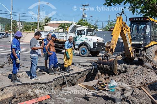 Funcionários da Companhia Estadual de Águas e Esgotos (CEDAE) fazendo o reparo na tubulação de esgoto por entupimento de gordura na esquina da Rua Rua Alberto Santos Dumont com a Rua Álvares de Castro  - Maricá - Rio de Janeiro (RJ) - Brasil