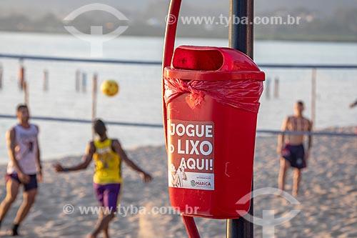 Detalhe de lixeira na orla da Lagoa de Araçatiba com praticantes de futevôlei ao fundo  - Maricá - Rio de Janeiro (RJ) - Brasil