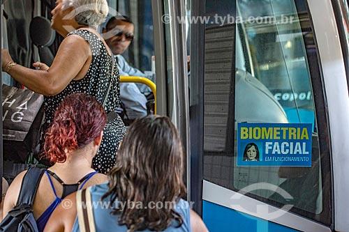 Passageiros embarcando em ônibus na Rodoviária do Povo de Maricá - antigo Terminal Rodoviário Jacinto Luis Caetano - com adesivo informando a utilização de sistema de Biometria Facial  - Maricá - Rio de Janeiro (RJ) - Brasil