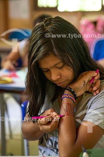 Aluna fazendo pintura corporal indígena com caneta hidrográfica na Escola Municipal Indígena Bilíngue Guarani Kyringue Aranduá (Português - Guarani)  - Maricá - Rio de Janeiro (RJ) - Brasil