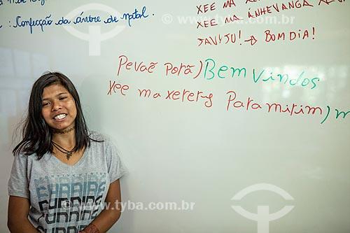 Aluna indígena ao lado de frases em Português e Guarani na Escola Municipal Indígena Bilíngue Guarani Kyringue Aranduá (Português - Guarani)  - Maricá - Rio de Janeiro (RJ) - Brasil