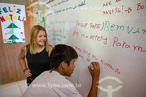 Professora e aluno indígena escrevendo frases em Português e Guarani na Escola Municipal Indígena Bilíngue Guarani Kyringue Aranduá (Português - Guarani)  - Maricá - Rio de Janeiro (RJ) - Brasil