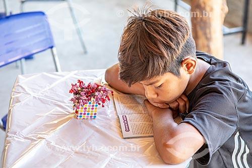 Aluno indígena lendo na Escola Municipal Indígena Bilíngue Guarani Para Poty Nhe Já (Português - Guarani) na Aldeia Mata Verde Bonita (Tekoa Ka Aguy Ovy Porã) da Tribo Guarani  - Maricá - Rio de Janeiro (RJ) - Brasil