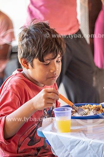 Aluno indígena almoçando durante a festa de encerramento do ano letivo na Escola Municipal Indígena Bilíngue Guarani Para Poty Nhe Já (Português - Guarani)  - Maricá - Rio de Janeiro (RJ) - Brasil