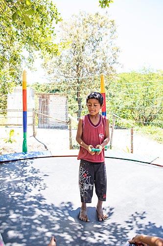 Aluno indígena brincando com jogo eletrônico em cama elástica durante a festa de encerramento do ano letivo na Escola Municipal Indígena Bilíngue Guarani Para Poty Nhe Já (Português - Guarani)  - Maricá - Rio de Janeiro (RJ) - Brasil
