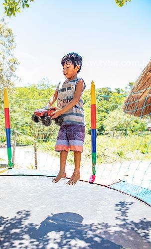 Aluno indígena com carrinho brincando em cama elástica durante a festa de encerramento do ano letivo na Escola Municipal Indígena Bilíngue Guarani Para Poty Nhe Já (Português - Guarani)  - Maricá - Rio de Janeiro (RJ) - Brasil