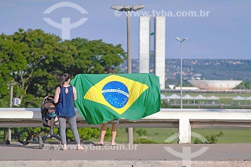 Família com bandeira do Brasil durante a cerimônia de posse presidencial de Jair Bolsonaro com o Congresso Nacional ao fundo  - Brasília - Distrito Federal (DF) - Brasil