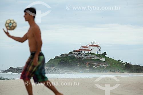 Banhista jogando futebol (altinha) na orla da Praia de Itaúna com a Igreja Nossa Senhora de Nazareth (1837) ao fundo  - Saquarema - Rio de Janeiro (RJ) - Brasil