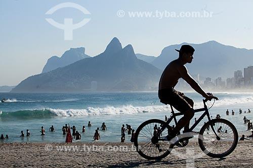 Ciclista na orla da Praia do Arpoador com o Morro Dois Irmãos e a Pedra da Gávea ao fundo  - Rio de Janeiro - Rio de Janeiro (RJ) - Brasil