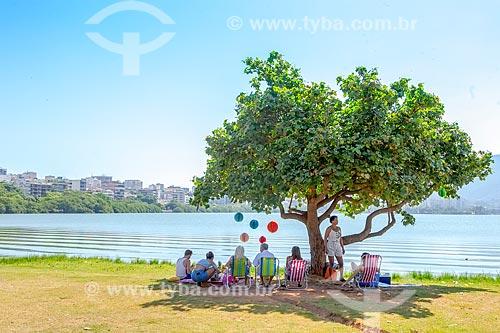 Pessoas protegendo-se do sol em sombra de árvore durante festa de aniversário às margens da Lagoa Rodrigo de Freitas  - Rio de Janeiro - Rio de Janeiro (RJ) - Brasil